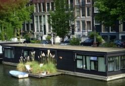 houseboat in a canal in Amsterdam with a deck, chair, and rowboat