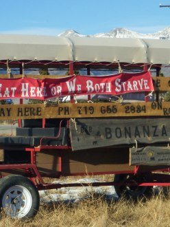 a wagon in front of a restaurant with a sign: Eat Here or We Both Starve