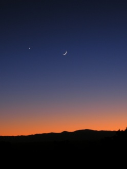 the moon and Venus over mountains