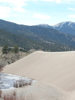 A sand dune, mountains, and a stream in Great Sand Dunes National Park