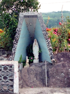 a shrine in central Costa Rica featuring Mary with flowers in the background