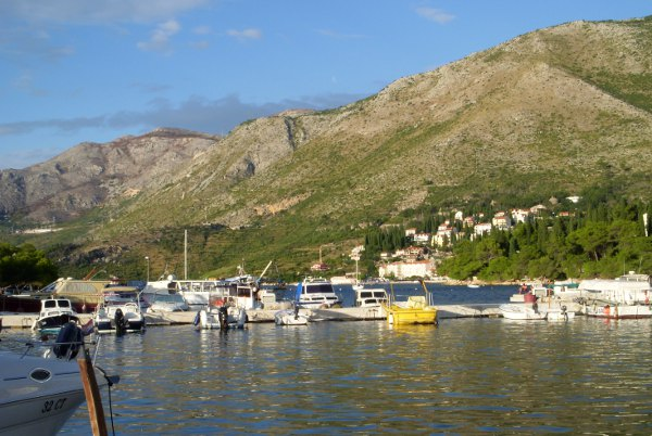 boats in a harbor on Croatia's coast with a village in the background