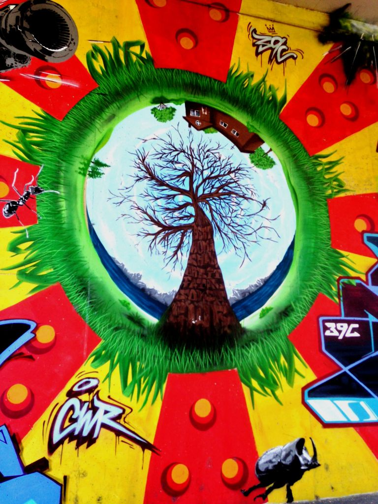 street art in Bolzano, Italy, with a nature scene in the middle surrounded by bright colors and graffiti